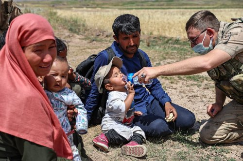 Turkish security forces gives water to a kid after irregular migrants were caught at the border with Iran in Van, Turkey on August 06, 2021 [Özkan Bilgin/Anadolu Agency]