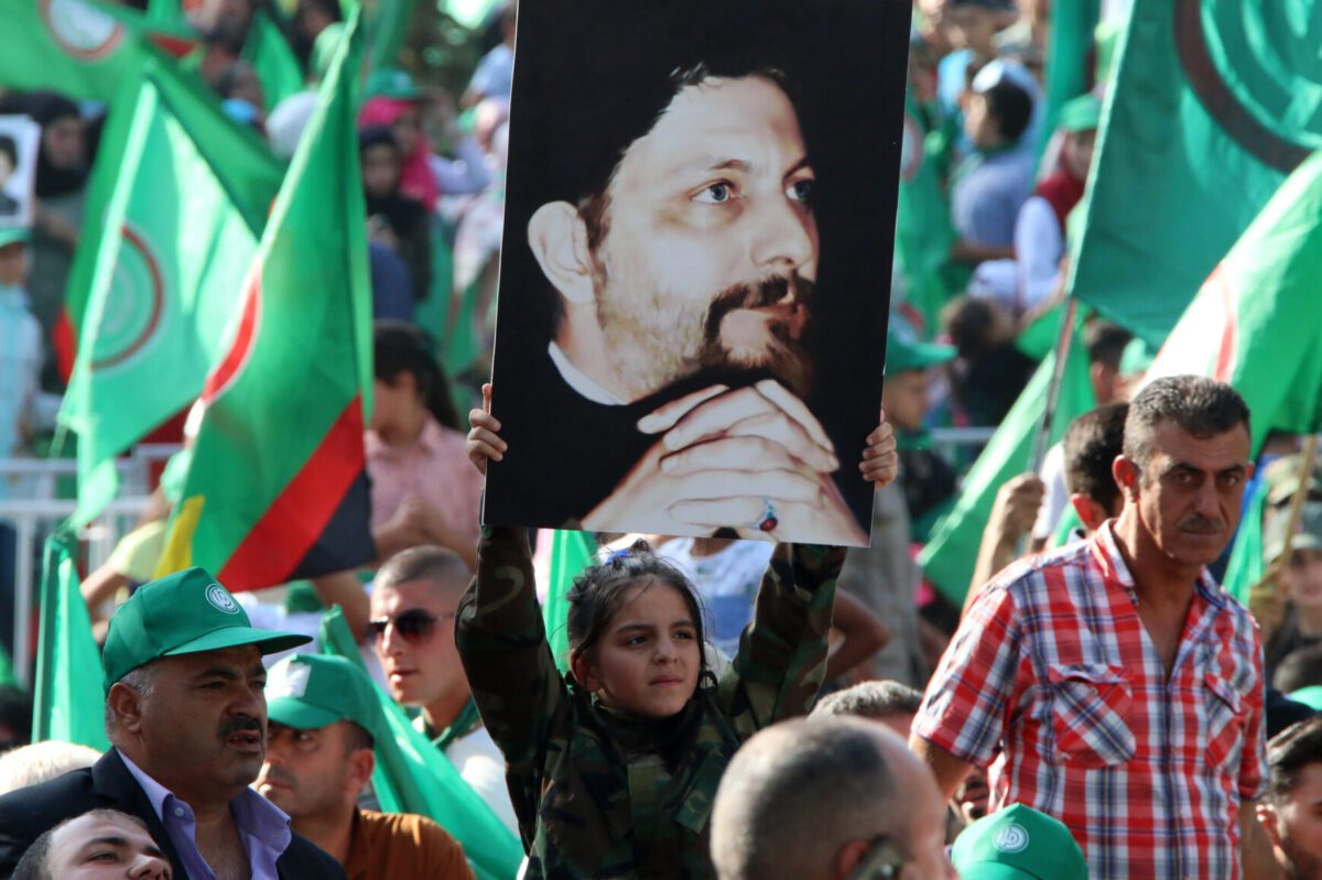Amal movement supporters hold up pictures of Imam Musa al-Sadr in Beirut on August 31, 2018 [STR/AFP via Getty Images]