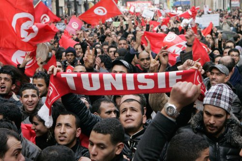 Tunisian expatriates shout slogans while holding Tunisian flags as they demonstrate on January 15, 2011 in Paris, France. [Franck Prevel/Getty Images]