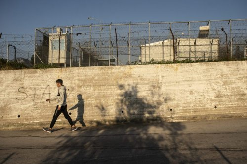 A migrant walks in front of the walls of the Moria refugee camp on February 2, 2020 in Moria, Greece [Ivan Romano/Getty Images]