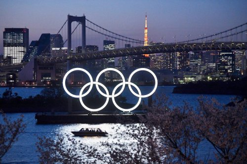 boat sails past the Tokyo 2020 Olympic Rings on March 25, 2020 in Tokyo, Japan. [Carl Court/Getty Images]