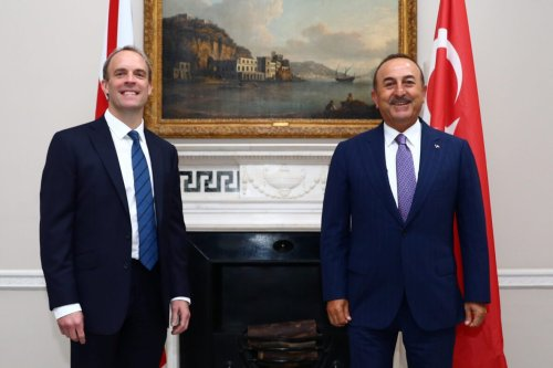Britain's Foreign Secretary Dominic Raab (L) reacts as he poses for a photograph with Turkey's Foreign Minister Mevlut Cavusoglu, at Carlton Gardens in London, on July 8, 2020, ahead of their meeting. (Photo by HANNAH MCKAY / POOL / AFP) (Photo by HANNAH MCKAY/POOL/AFP via Getty Images)