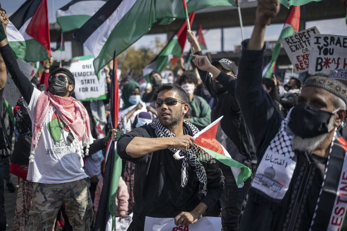 Protesters gather and hold Palestinian flags in central Johannesburg, on May 23, 2021, as they take part in a counter protest in solidarity with Palestinians in response to a demonstration organised by the South Africa Zionist Federation. [MICHELE SPATARI/AFP via Getty Images]