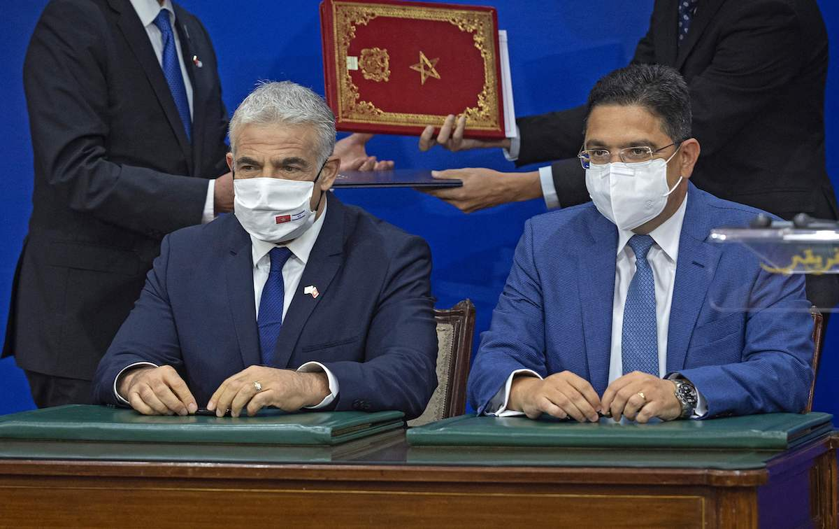 Moroccan Foreign Minister Nasser Bourita (R) sits near his Israeli counterpart Yair Lapid after signing documents, in Rabat, on 11 August 2021 [FADEL SENNA/AFP via Getty Images]