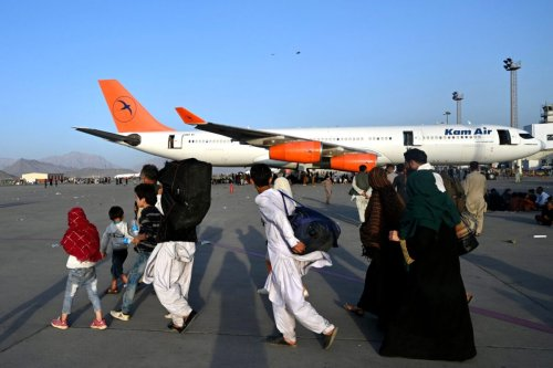 Afghan families walk by the aircrafts at the Kabul airport in Kabul on August 16, 2021, after a stunningly swift end to Afghanistan's 20-year war, as thousands of people mobbed the city's airport trying to flee the group's feared hardline brand of Islamist rule. (Photo by Wakil Kohsar / AFP) (Photo by WAKIL KOHSAR/AFP via Getty Images)