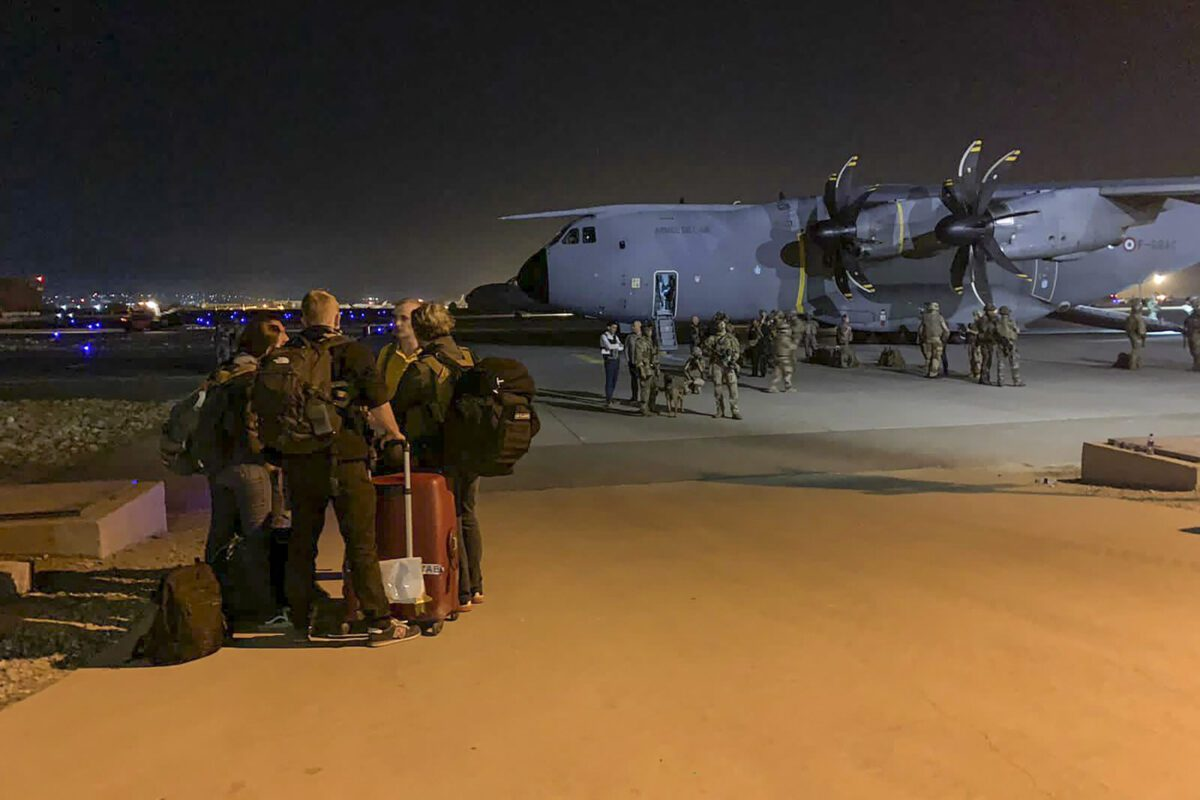 People wait to board a military transport plane at the airport in Kabul on August 17, 2021 [STR/AFP via Getty Images]