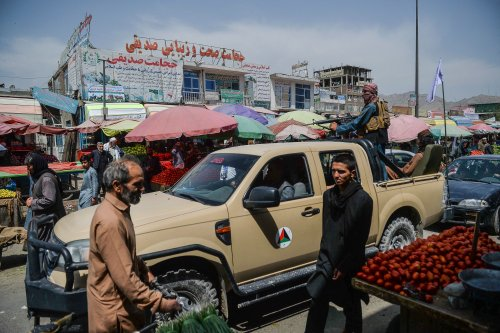 Taliban fighters on a pick-up truck move around a market area, flocked with local Afghan people at the Kote Sangi area of Kabul on August 17, 2021 [HOSHANG HASHIMI/AFP via Getty Images]