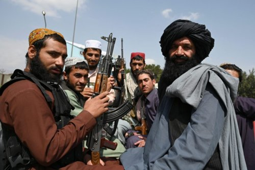 Taliban fighters sit on the back of a pick-up truck at the airport in Kabul on August 31, 2021 [WAKIL KOHSAR/AFP via Getty Images]