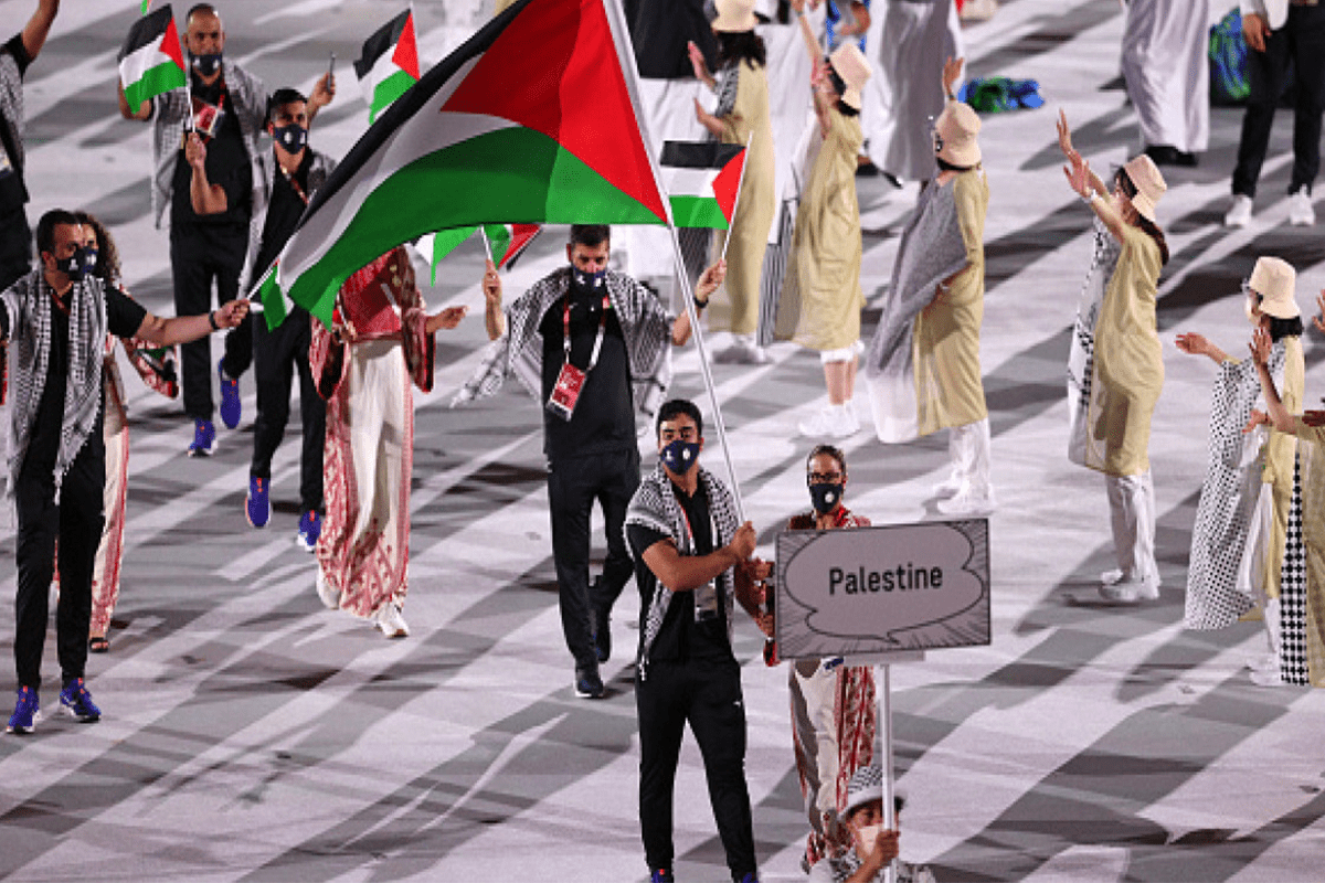 Team Palestine flagbearers Dania Nour and Mohammed K H Hamada carry the Palestinian flag during the 2020 Tokyo Summer Olympic Games opening ceremony at the Olympic Stadium in Tokyo, Japan [Stephen McCarthy/Sportsfile via Getty Images]