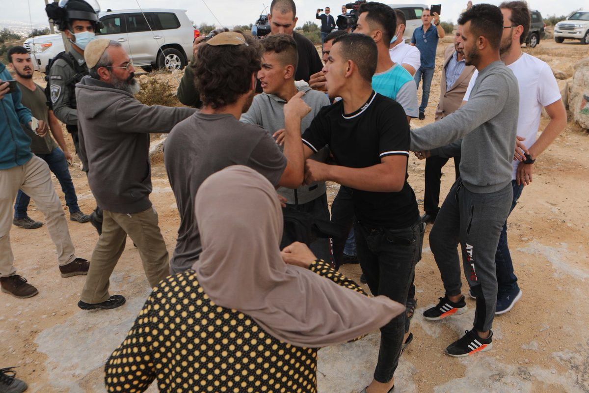 Jewish settlers attack Palestinians with wooden sticks and stones during European countries ambassadors visit to the district, at Susiya village in Hebron, West Bank on September 24, 2021 [Mamoun Wazwaz/Anadolu Agency]