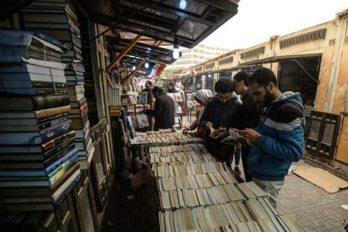 Men look through books on sale at Cairo's historic al-Azbakeya book market at downtown in Cairo on January 16, 2019. (Photo by Mohamed el-Shahed / AFP) (Photo credit should read MOHAMED EL-SHAHED/AFP via Getty Images)