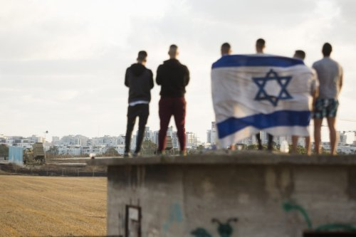 Israelis gather to watch the Iron Dome missile defence system launch to intercept rockets fire from the Gaza Strip on May 17, 2021 in Ashdod, Israel. [AHMAD GHARABLI/AFP via Getty Images]
