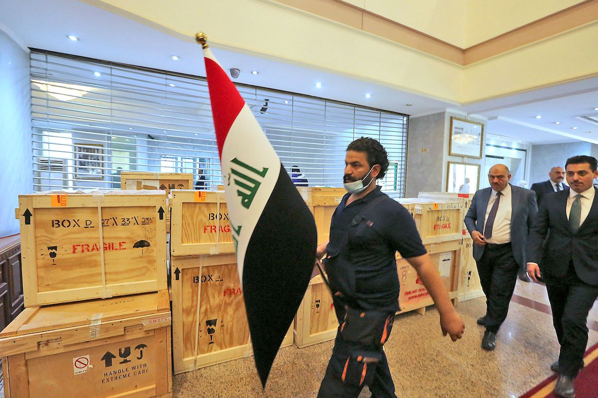 Staff members at Iraq's Ministry of Foreign Affairs work around crates of looted Iraqi antiquities returned by the United States, ahead of a handover ceremony at the ministry in the capital Baghdad, on 3 August 2021. [SABAH ARAR/AFP via Getty Images]