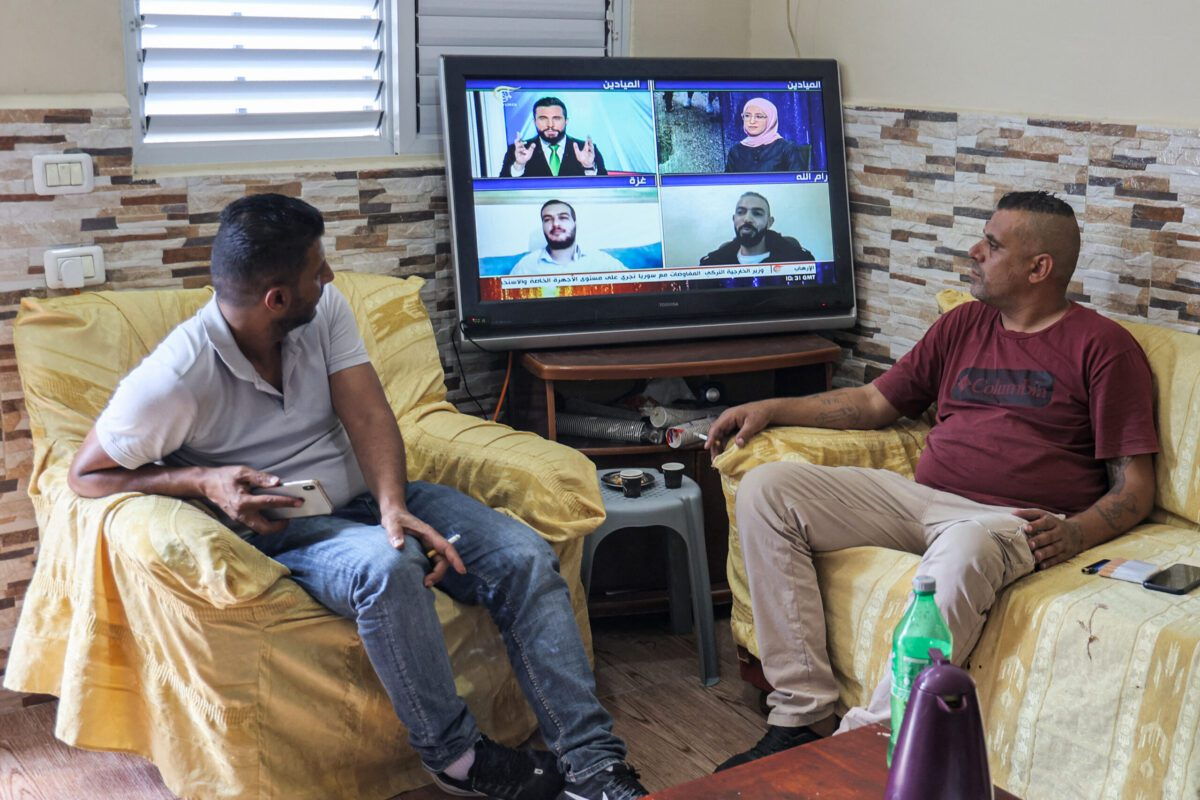 Family members of of Zakaria Zubeidi, one of six Palestinian prisoners who escaped from Israel's Gilboa prison, watch a news bulleting on a television on September 7, 2021 [JAAFAR ASHTIYEH/AFP via Getty Images]