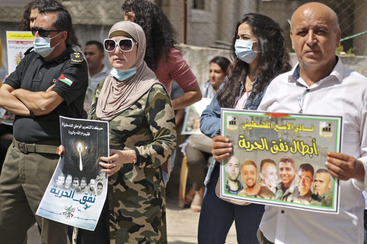 People gather with signs for a demonstration in support of Palestinian prisoners held in Israeli prisons, outside the offices of the International Committee of the Red Cross (ICRC) in Ramallah in the occupied West Bank on September 14, 2021 [ABBAS MOMANI/AFP via Getty Images]