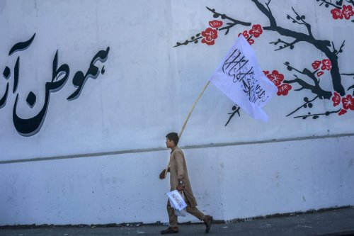 A boy walks along a street selling Taliban flags in Kabul on September 16, 2021 [BULENT KILIC/AFP via Getty Images]