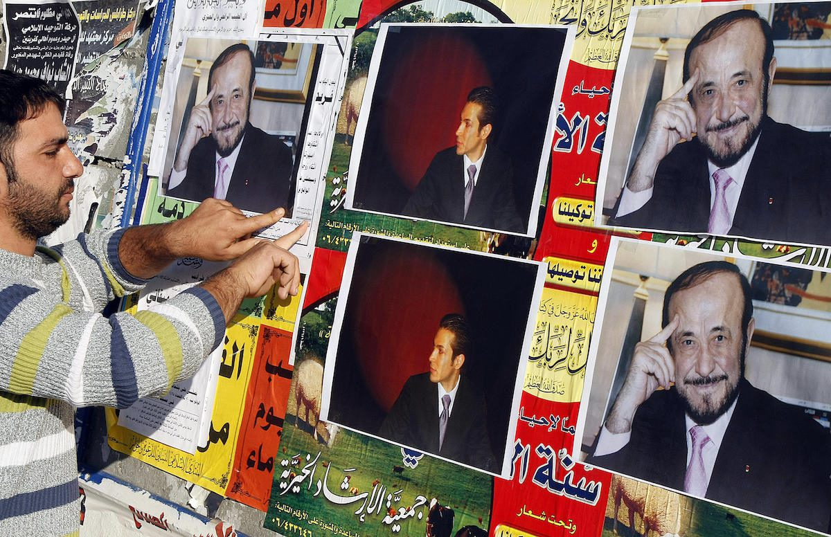 A member of the Alawite community pastes on a wall, in the northern Lebanese city of Tripoli 06 December 2007, pictures of Syrian opposition leader Rifaat al-Assad (R) and his son Ribal. Rifaat al-Assad is the younger brother of the late Syrian President Hafez al-Assad, and the uncle of the current one, Bashar al-Assad, all of whom come from the minority Alawite Muslim sect. [RAMZI HAIDAR/AFP via Getty Images]