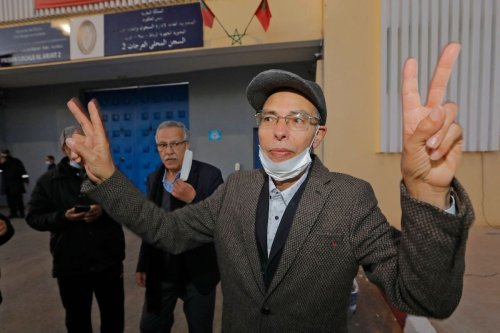 Moroccan historian and rights activist Maati Monjib (C), who was on hunger strike for 19 days, gestures upon his release from El Arjate prison near the capital Rabat on March 23, 2021. [STR/AFP via Getty Images]