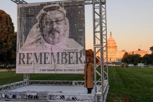 Turkish writer Hatice Cengiz (R), fiancée of Saudi journalist and dissident Jamal Khashoggi, poses next to a portrait of Khashoggi after unveiling it on the National Mall in Washington, DC., on October 1, 2021 [NICHOLAS KAMM/AFP via Getty Images]