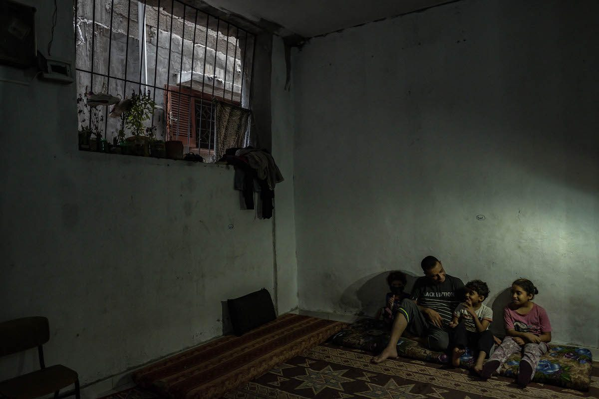 Mohammad al-Taramsi sits with his children in his house under the LED light due to ongoing power cuts in Jabalia Refugee Campon August 29, 2020 in Gaza City, Gaza. on August 29, 2020 in Gaza City, Gaza. [Fatima Shbair/Getty Images]