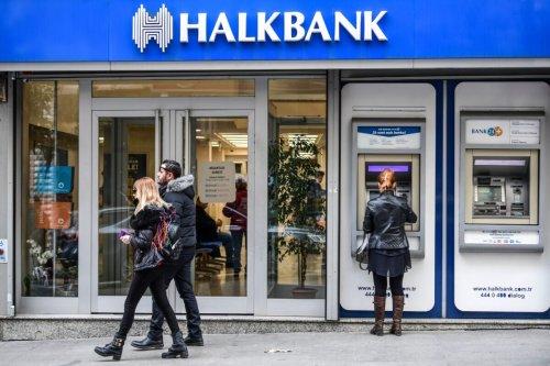 People walk past a branch of Halkbank on December 1, 2017 in Istanbul, Turkey [OZAN KOSE/AFP via Getty Images]