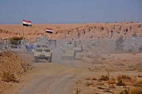 Iraqi forces gather near the crossing between Syria and Iraq on 1 November 2018 [MOADH AL-DULAIMI/AFP/Getty Images]