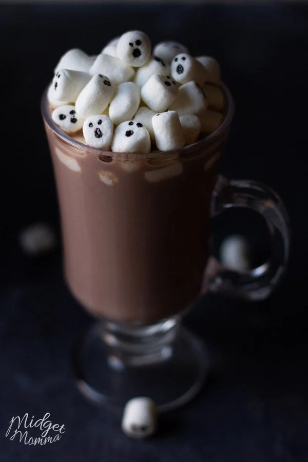 Homemade hot chocolate in a clear mug with marshmallows on top with ghosts faces on them