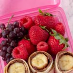 Close up shot of Nutella And Banana Sushi roll up in a pink lunch box container with grapes, strawberries and raspberries