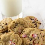 Chocolate chip cookies made with candy canes in a pile and a glass of milk.