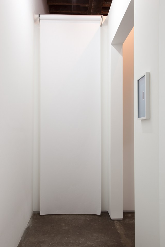 David Catherall, installation view. Left: J , 2012. Paper roll, steel roll dispenser. 120 x 36 inches. Right: CTHRLL DVD, 2011-2012. Laser cut metal door handle prototype, artist frame. 2 x 1 x ⅛ inches; 10 ¼ x 13 ½ inches framed