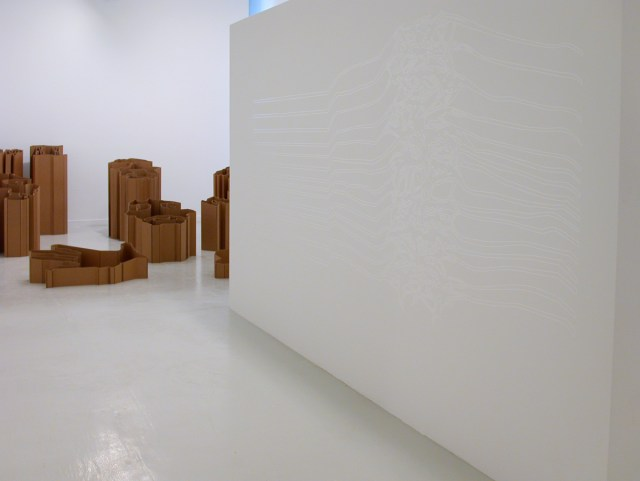 "Jay Heikes and Kirk McCall, installation view. Left: Kirk McCall, Queen II, 2002. 2-ply cardboard. Dimensions variable. Right: Jay Heikes, The Joy Division, 2001. Vinyl. 52"" x 124"". Edition of 1."