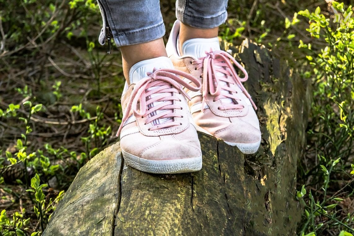 pink shoes balancing on a wooden log