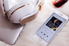 Audio book and headphones make reading easier for moms with migraine.