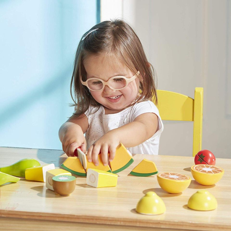 A girl cutting wooden foods while playing pretend.