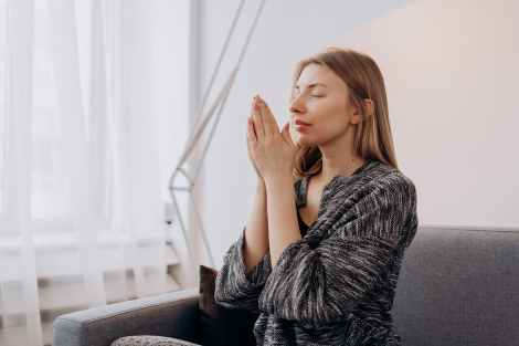 woman with her hands together rubbing essential oils between her palms and breathing deeply