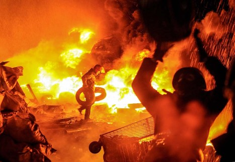 Protesters burn tires as they clash with riot police.