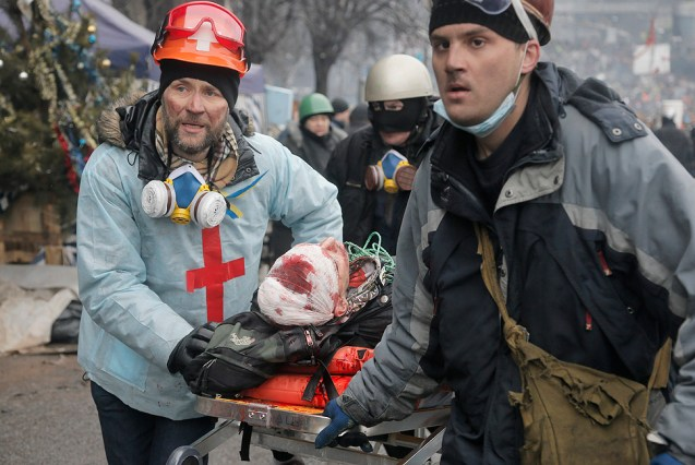 A wounded Ukrainian protester is evacuated during clashes with police in Kiev's Independence Square.