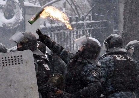 A Ukrainian police officer throws a Molotov cocktail during clashes with protesters in Kiev on Jan. 22, 2014.