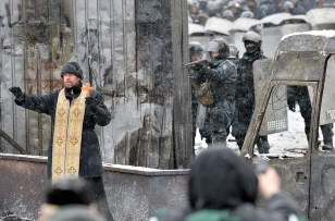 An Orthodox priest tries to stop clashes between protesters and police in Kiev on Jan. 22, 2014.
