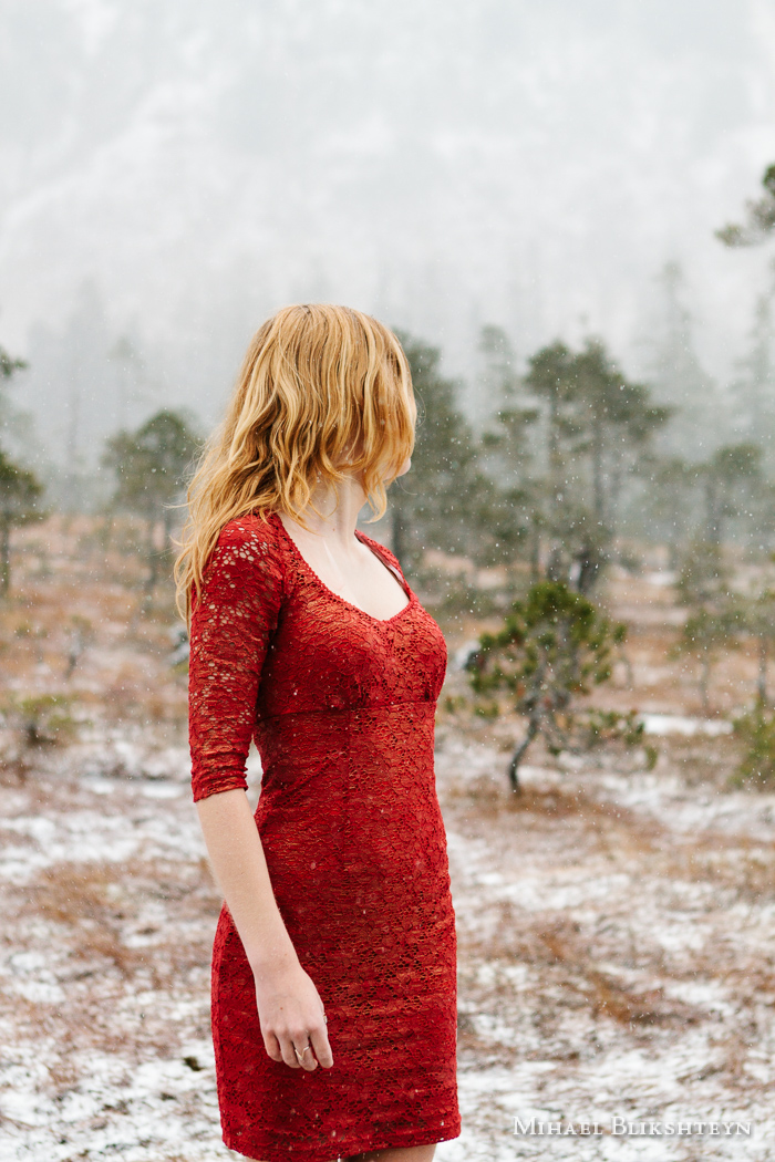 Young woman in red dress looking back from the camera at trees i