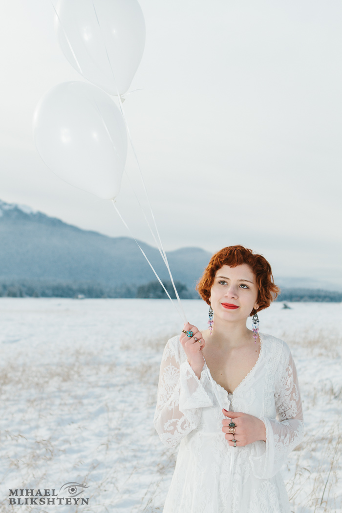 Young woman in white dress holding white balloons on a white snow-covered meadow