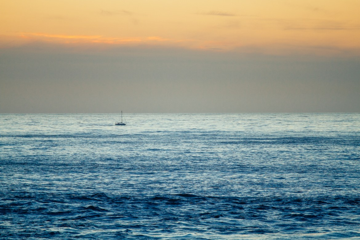 Lone sailboat in the calm, open ocean at sunset