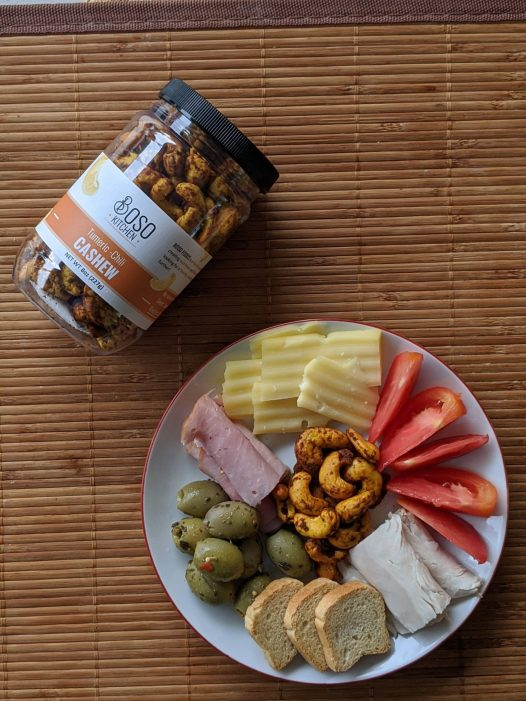 A ohoto of turmeric cashews displayed in a mii cheese plate that includes tomatoes, olives, turkey and cheese.