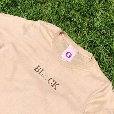 "tan shirt with ""black"" embroidered on the center"