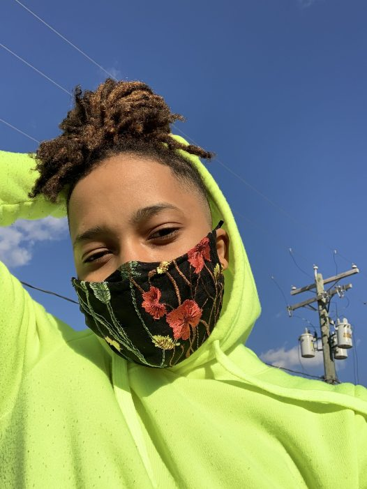 A black woman with locs wearing a neon green hoodie with a black mask with embroidered red and pink flowers and green leaves on it.