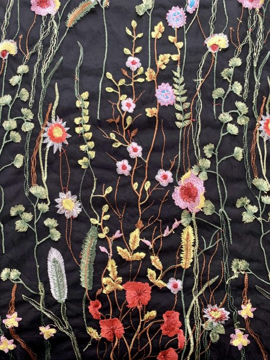 Black fabric with colorful embroidered flowers