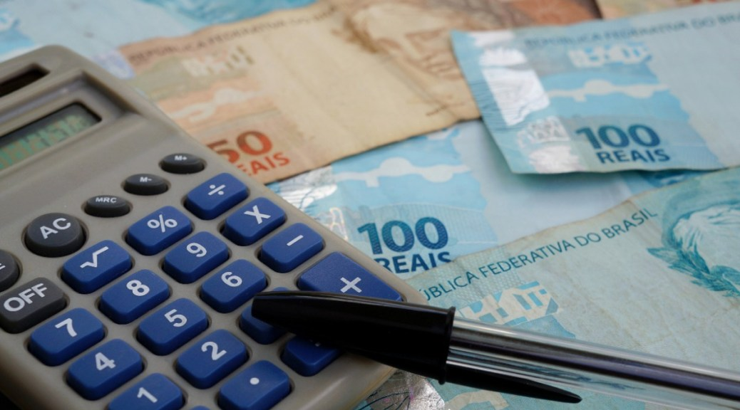 Rekenmachine met een pen en Braziliaanse real biljetten
