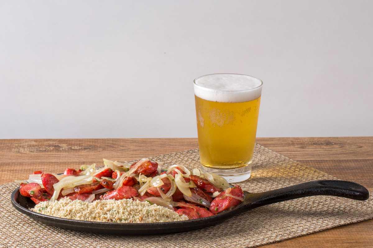 Braziliaanse Linguiça Calabresa Acebolada com Farofa op een bakje naast een glas met bier