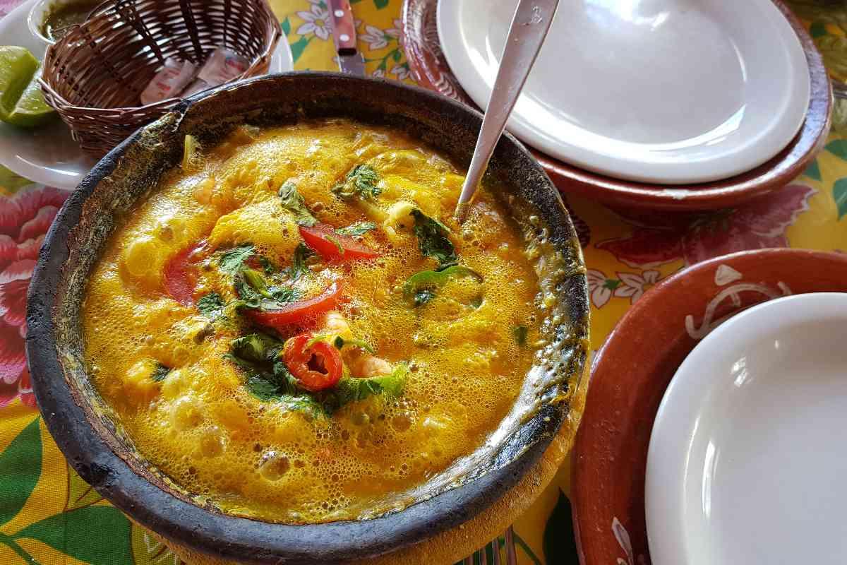 Moqueca de Camarão in een grote kom met een lepel en borden er om heen