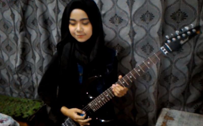 Jonge moslim meisje speelt cover Judas Priest op gitaar